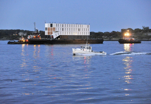 Tugboats tow a barge carrying a mystery structure into Portland Harbor at dusk Thursday. The structure was assembled on the barge in New London, Conn., and was headed for a Cianbro Corp. facility off Commercial Street in Portland, where it is scheduled for a significant amount of interior work before it is delivered to its owner.