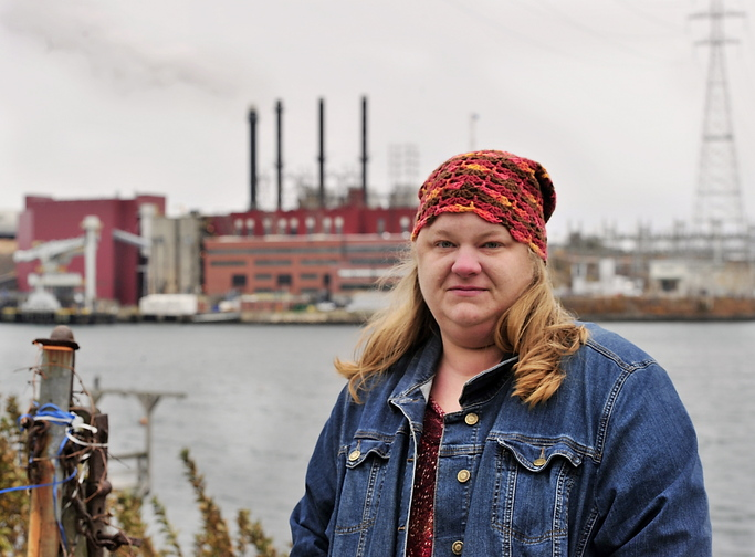 Kim Richards, founder of Citizens for Clean Air, stands across the Piscataqua River from the Schiller Station's four smokestacks.