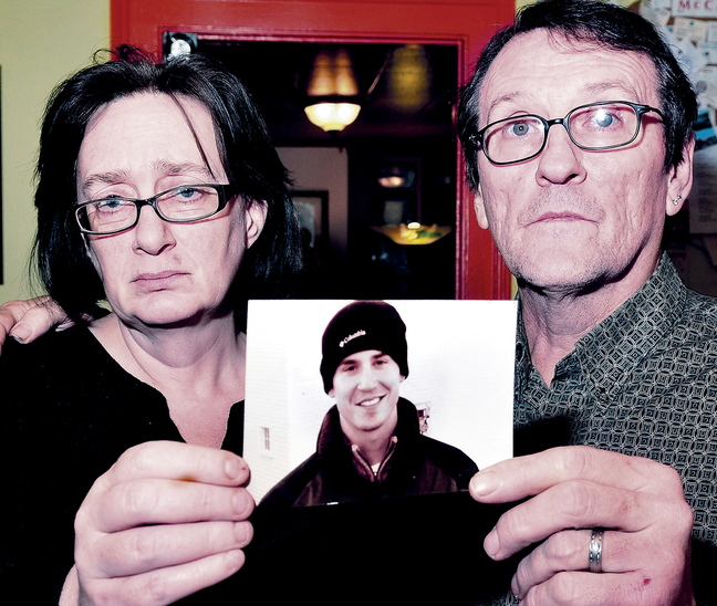 Lorna and Michael Smilek hold a photograph of Michael's son, Justin Crowley-Smilek, a troubled U.S. Army veteran who was shot and killed by Farmington police in 2011.