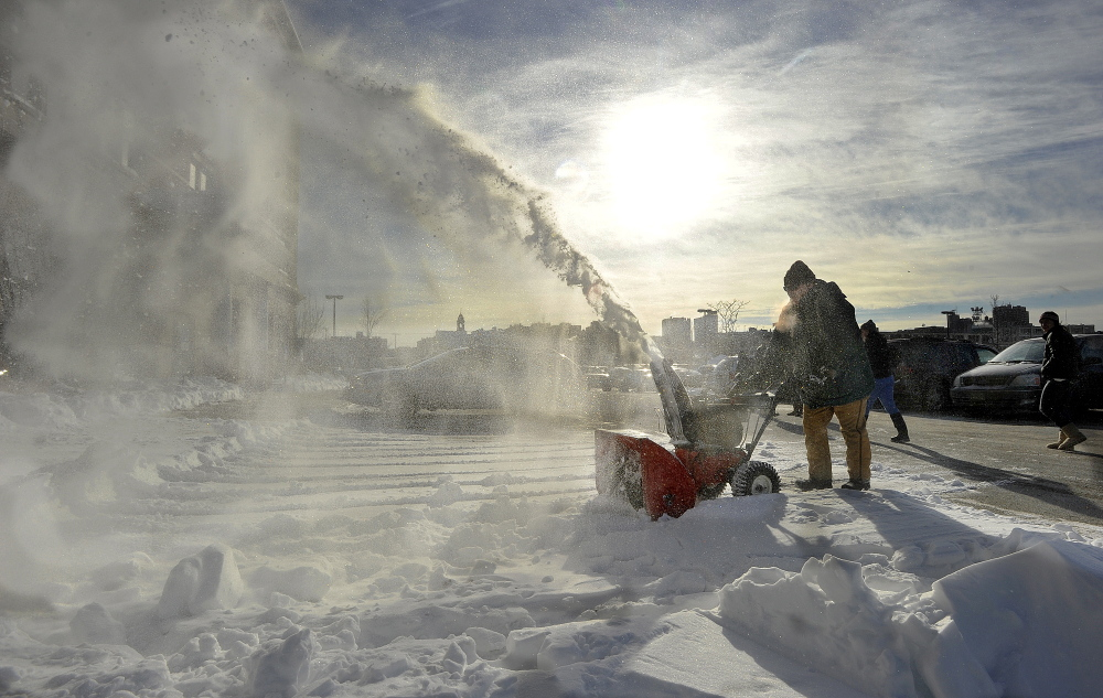 An employee uses a snowblower to clear the parking lot at the Department of Health and Human Services on on Marginal Way in Portland on Tuesday, just in time for more snow that is headed for Maine.