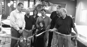 JASON AGREN, president of Agren, watches with Agren employees as his daughter Sarah, center, cuts the ribbon during a ceremony Friday to celebrate the grand opening of the Auburn-based family-owned company's new Topsham store at 78 Mallett Drive.