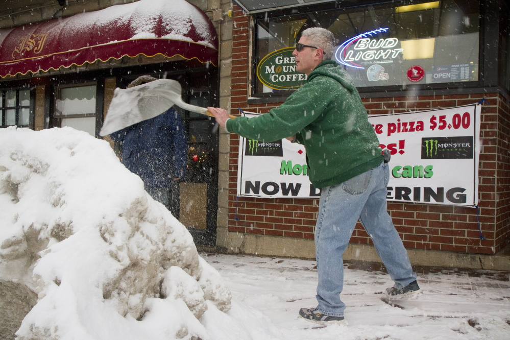 Congress Street Variety night manager Stephen Brichetto clears the latest snowfall in front of the Portland store on Tuesday. The lower back is the body part most frequently injured while shoveling.