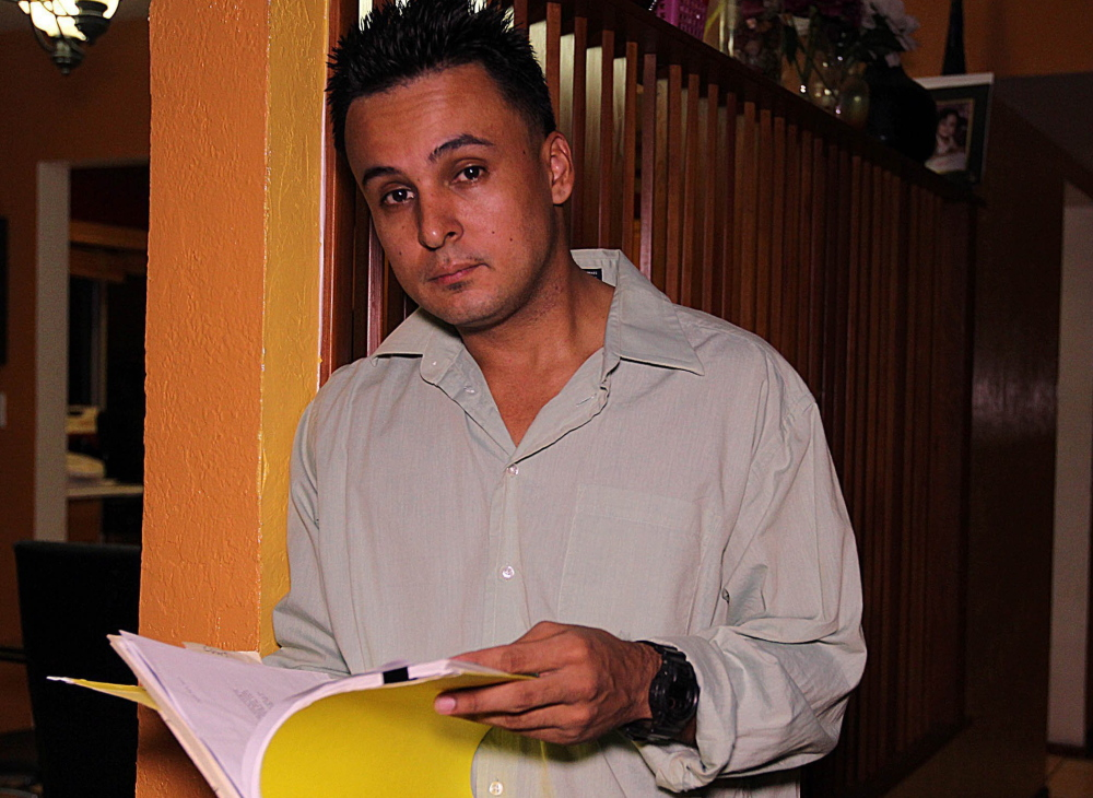Carlos M. Gomez looks over documents in his Kendall, Fla., home Jan. 30. He was wrongfully arrested in 2011 and accused of laundering Wachovia bank costumers' money through an account bearing his name. A bank employee had created the false account.