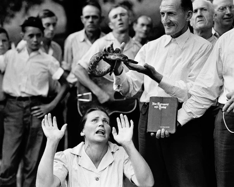 """In this Aug. 22, 1944 file photo, members of the Pentecostal Church of God, a faith healing sect, surround a woman who has """"Got the Spirit"""" as a man holds a snake above her head in Evarts, Ky. Although a Kentucky statute passed in 1940 prohibits the handling of snakes in connection with religious services, this sect revived the ritual after the recent death of a native of the region who was bitten by rattlesnake. 1940s 40s Animal Back Woods Bible Book Charmer Christians Cult Danger Eerie Event Fear Guitar Handler Kneeling Men Odd Offbeat Religion Risk Rural Sect Serpent Snake Speaking in Tongues Spirituality Standing State Strange Trance Trust Watching Women"""