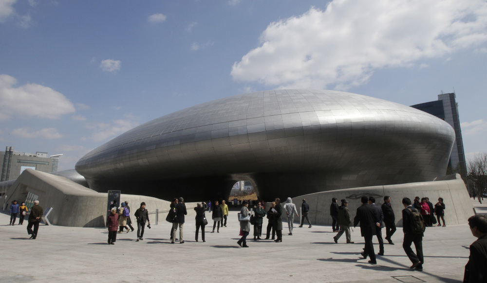 Visitors are dwarfed by Dongdaemun Design Plaza in Seoul, South Korea.