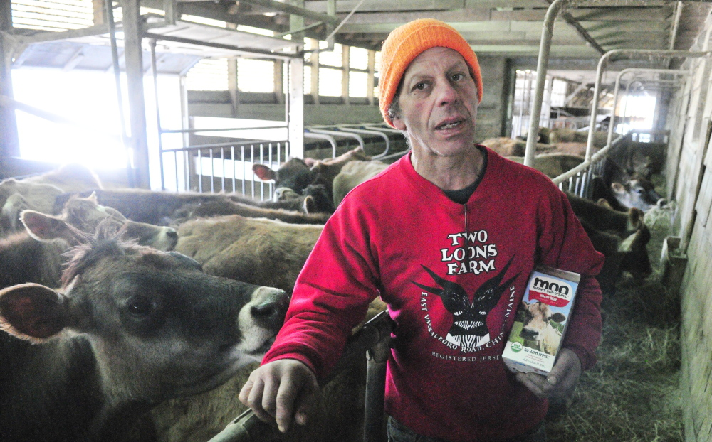 Spencer Aitel holds a redesigned container of MOOMilk at Two Loons Farm in South China. He owns the 150-cow organic farm with his wife, Paige Tyson.