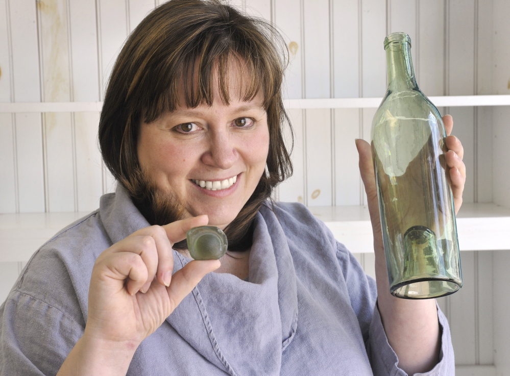 "Danielle Perreault holds a ""kick up"" piece of sea glass similar to the one in a circa 1800s wine bottle. Former first lady Barbara Bush plans to donate sea glass collected at Walker's Point to Perreault's new Sea Glass Center."