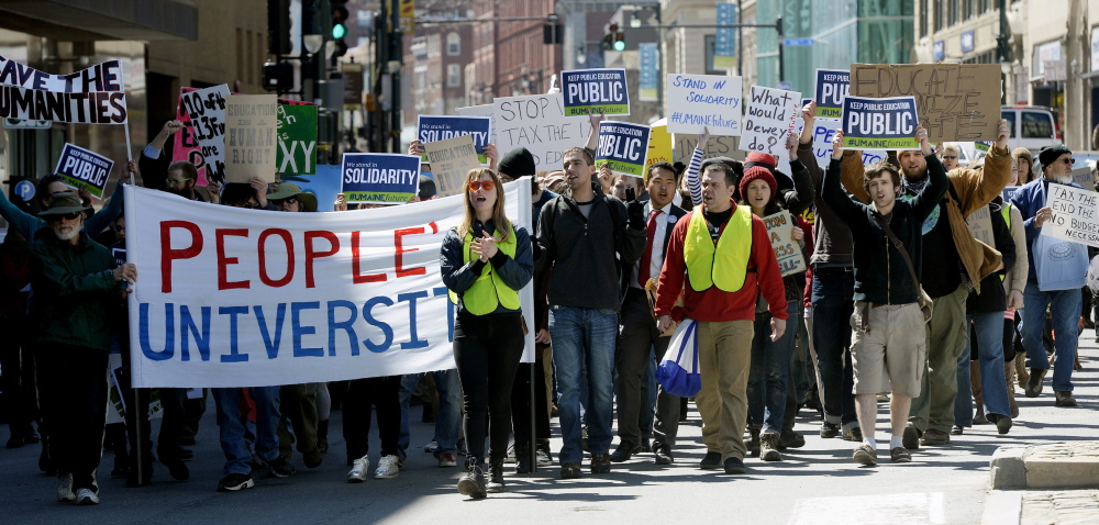 Protesters march down Congress Street to protest the budget cuts at the University of Southern Maine.