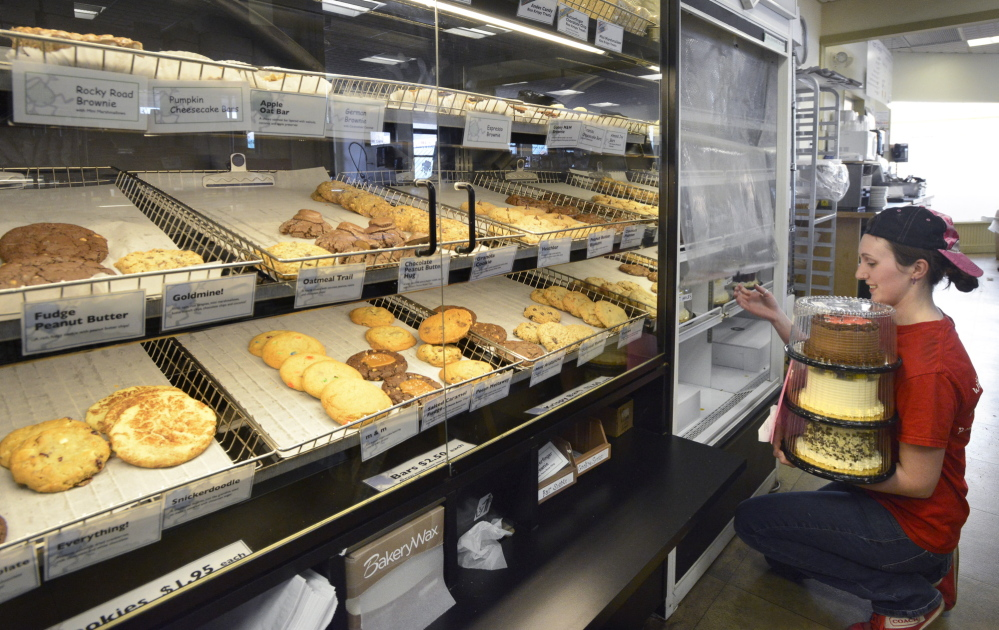Pastry chef Brooke MacArthur stocks the cake display at Wild Oats Bakery and Cafe, where everything is homemade.