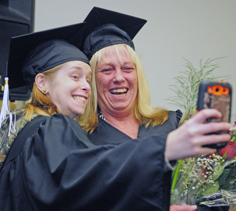 """Nicole """"Sis"""" Trask, left, takes a picture with her mother, Kathy Trask, on Saturday before they walked in the University of Maine at Augusta graduation ceremony."""