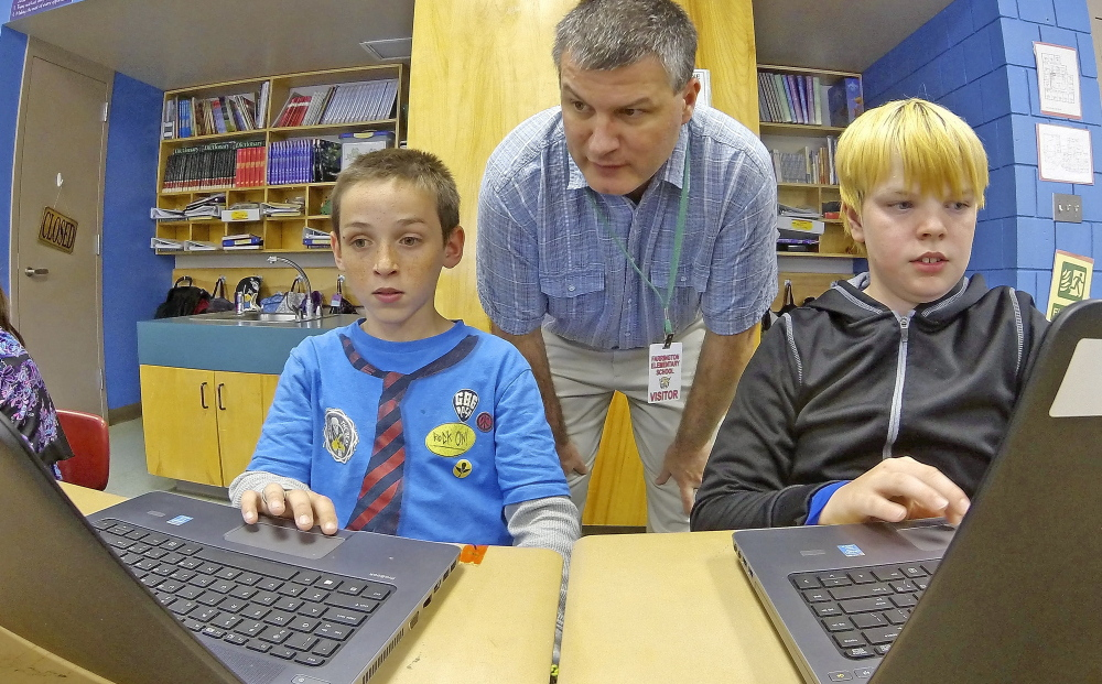 Tony Paine, CEO of Kepware Technologies, center, chats with fourth-graders Gabriel Biasuz, left, and Jared Barker about how they use the laptops that his company donated, on Friday at Farrington Elementary School in Augusta. Joe Phelan/Kennebec Journal