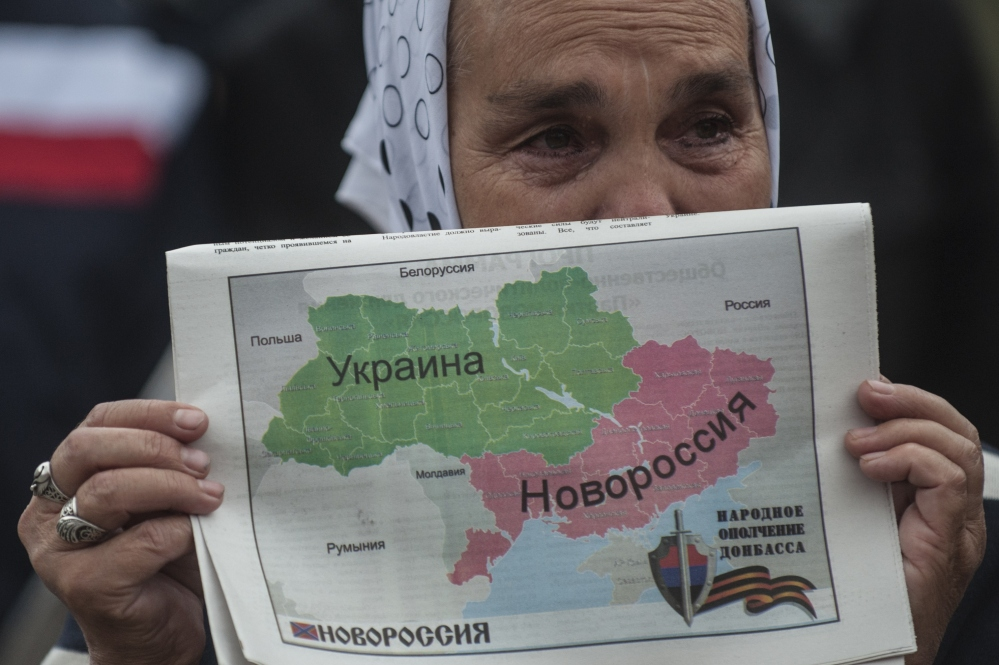 A woman holds a map showing Ukraine divided into two parts – the eastern part labeled Novorossia, or New Russia – during a rally in Donetsk, Ukraine, on Wednesday.