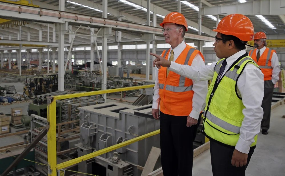 In this August 2013 photo provided by the Alabama Governor's office, Gov. Robert Bentley, left, listens to Roger Zhang, Golden Dragon U.S.A. President, during a tour of the new Golden Dragon copper tubing plant, then under construction, in Pine Hill, Ala. Golden Dragon, the first company Bentley recruited to Alabama after being elected, will employ 300 new full-time employees in rural Wilcox County.