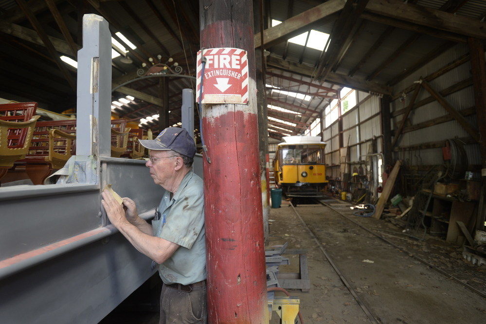 """Don Curry, the restoration project manager at the Seashore Trolley Museum, sands the side of the 1906 Montreal """"Golden Chariot"""" observation car at the Seashore Trolley Museum in Kennebunkport on Thursday."""