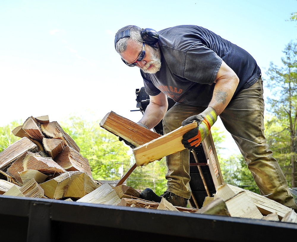 Mark Killinger, owner of Atlantic Firewood, arranges processed firewood in the bed of his truck in Windham on May 21. He and other dealers are receiving larger and earlier orders this year. Gordon Chibroski/Staff Photographer