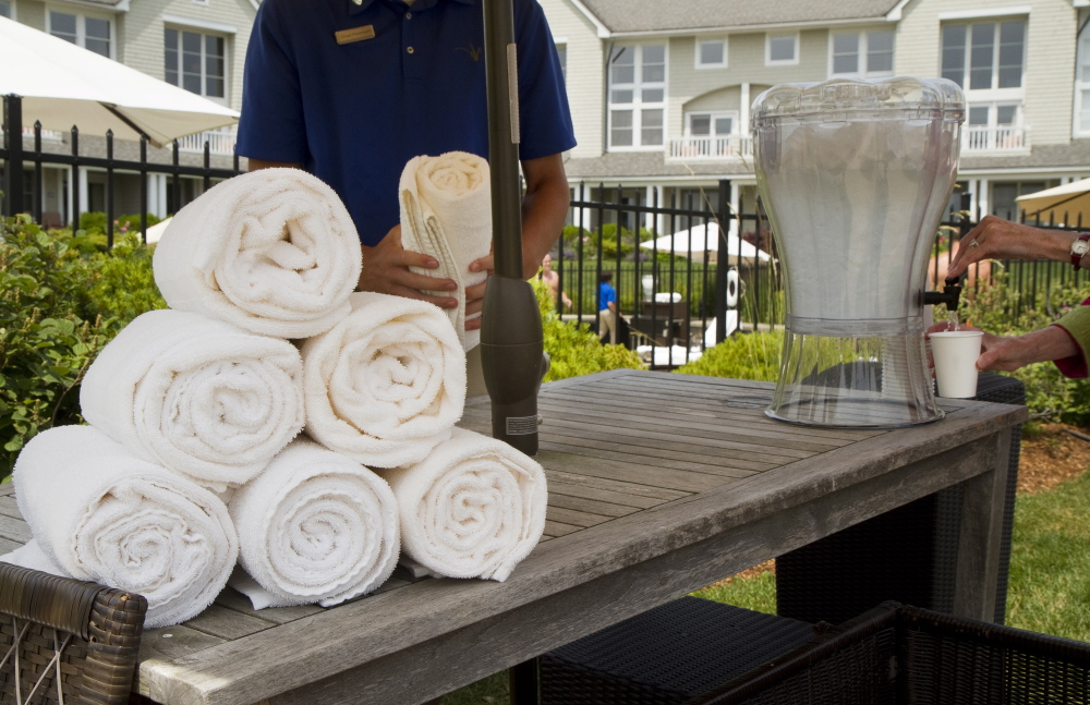 An Inn by the Sea staff member folds towels for guests by the pool. Business at Maine tourist hotspots is on its best pace since 2005. Carl D. Walsh/Staff Photographer