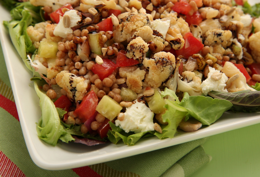 A colorful couscous salad with roasted cauliflower and dijon dressing will be a welcome surprise at a potluck gathering.