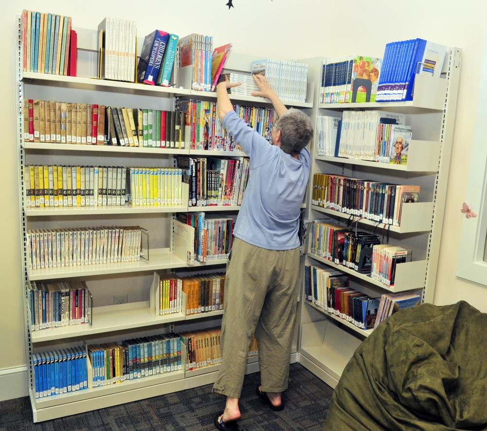 Board of trustees member Bonnie Dushin straightens books in the young adult area at the new Umberhine Public Library in Richmond.