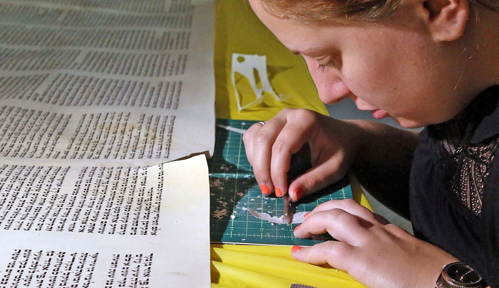 """Rachel Salston of Los Angeles, who is a """"soferet,"""" one of the country's few female scribes, repairs a damaged Torah used by the Jewish Academy of Orlando in Maitland, Fla."""