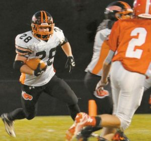 BRUNSWICK HIGH SCHOOL running back Will Bessey (28) looks for running room during a football game against Cony at Augusta on Friday. Bessey rushed for 245 yards in the Dragons' 52--27 victory.