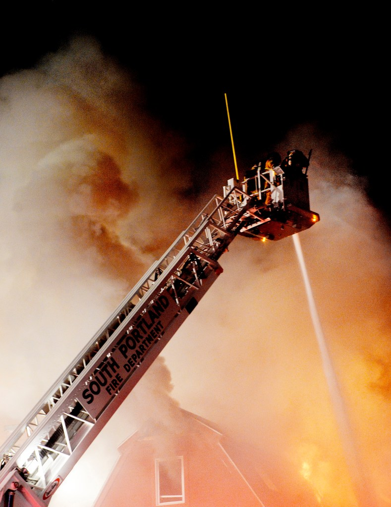 Firefighters spray water from above the flames at the Scarborough Commons building on Route 1 Monday night.