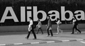 PEOPLE WALK PAST A COMPANY LOGO at the Alibaba Group headquarters in Hangzhou, in eastern China's Zhejiang province. Alibaba Group's U.S. stock offering is a wakeup call about an emerging wave of technology giants in China's state-dominated economy.