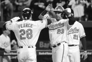 BALTIMORE'S Nelson Cruz (23) and Nick Markakis (21) greet teammate Steve Pearce at home plate after Pearce batted them in on a home run in the first inning of a baseball game against the Toronto Blue Jays on Tuesday in Baltimore. The Orioles clinched their first A.L. East title since 1997.