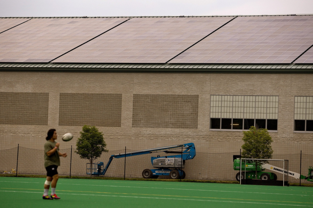 Josh Kim, a junior at Bowdoin College, tosses a rugby ball in front of newly installed solar panels atop Watson Arena in Brunswick last month. 2014 Press Herald File Photo/Gabe Souza