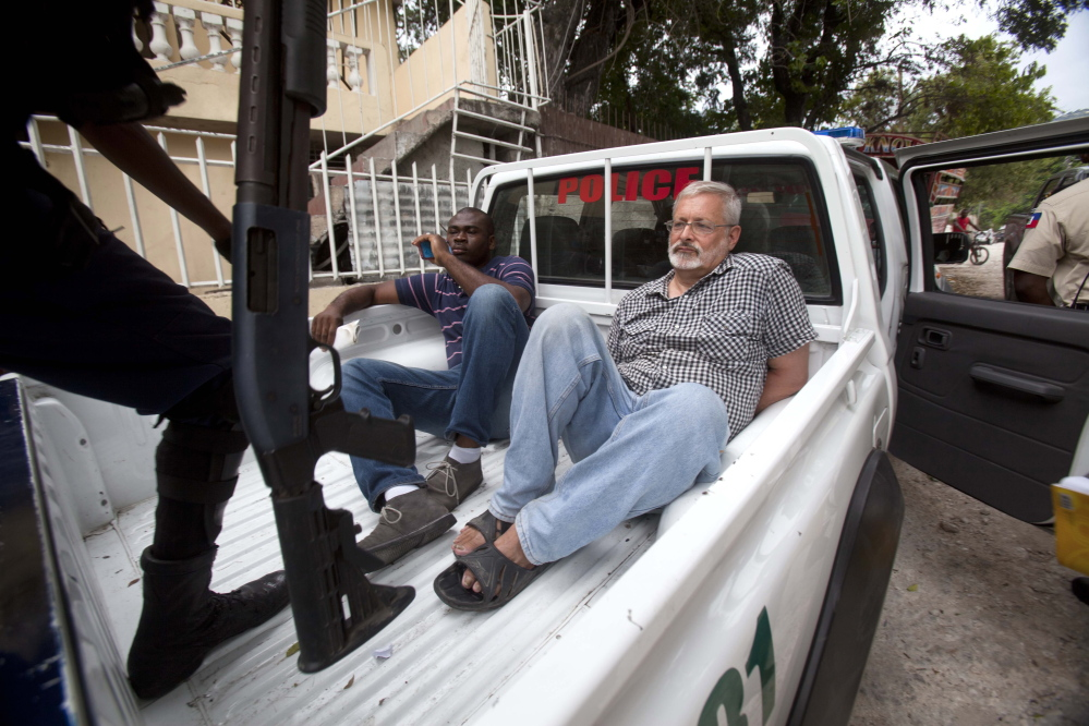 Michael Geilenfeld waits in handcuffs as the manager of his orphanage sits with him in the back of a police truck outside the St. Joseph's Home For Boys after police closed it down in Port-au-Prince, Haiti, on Friday.