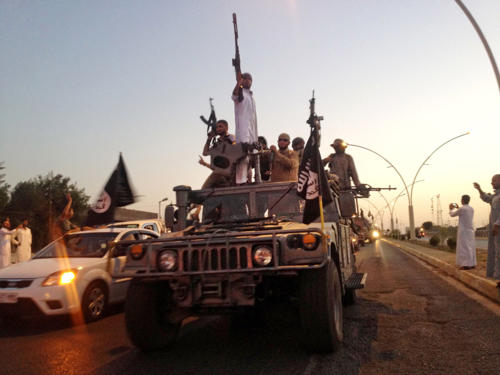 In this photo taken June 23, fighters from the Islamic State group parade in a commandeered Iraqi security forces vehicle down a main road at the northern city of Mosul. The Islamic State is often described as the most fearsome jihadi outfit of all, but it is no unstoppable juggernaut.
