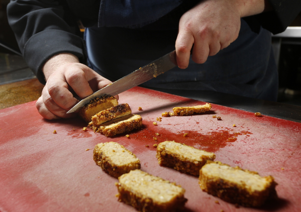 Grace chef Adam Flood slices tempeh.
