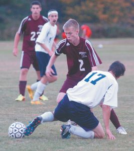 RICHMOND'S CAMERON EMMONS (2) moves around Pine Tree Academy defender Kenny Sweetser (17) during a boys high school soccer game in Freeport on Thursday. Emmons scored a goal in the Bobcats' 2-0 non-conference win.