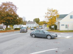 A GROUP PARTICIPATING IN A WALK AUDIT in the Lower Village of Topsham Monday morning see the backup of vehicles after a car had stopped to let the audit group pass through the entrance of the Bowdoin Mill Island.