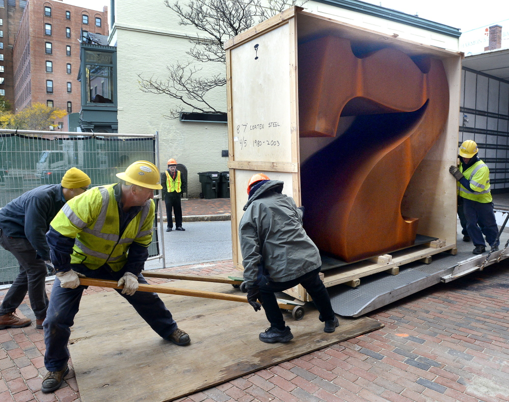 """Workers get ready to install the """"Seven"""" sculpture by Robert Indiana outside of the Portland Museum of Art. """"This is a public announcement that 7 Congress Square will always be a place for art,"""" the chief curator says"""