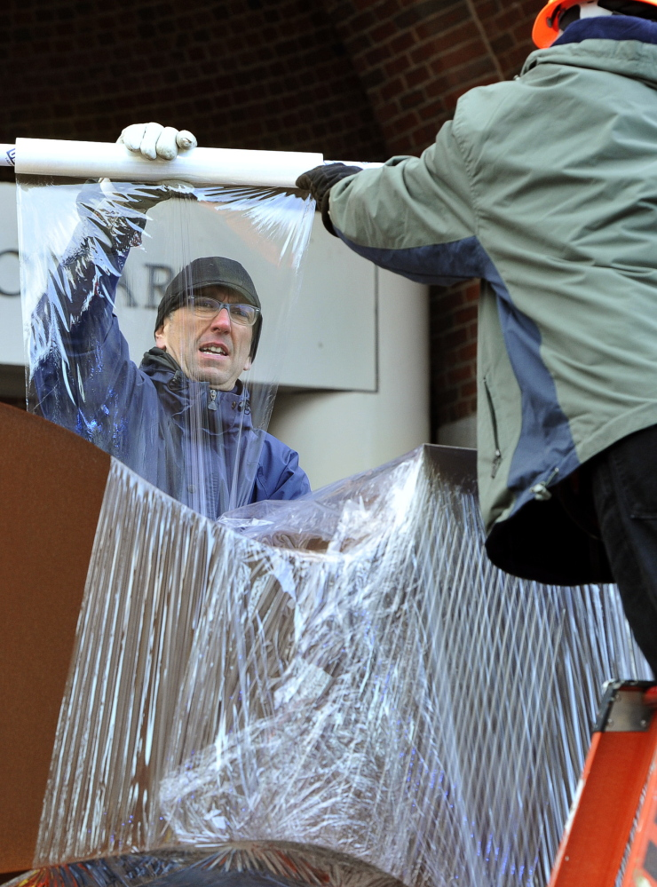 Kris Kenow and Greg Welch shrink-wrap the sculpture before it is lifted by a crane.