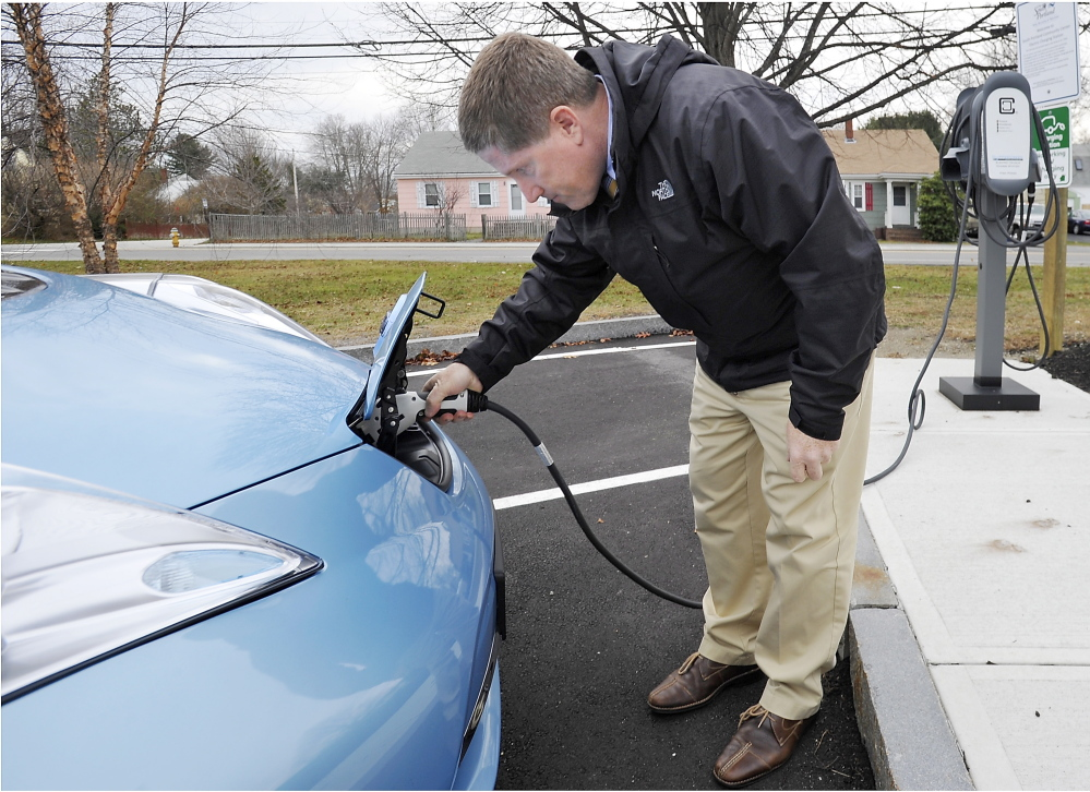 """City Manager Jim Gailey charges the city's new Nissan Leaf. """"You gotta have the infrastructure in place ... for people to operate electric vehicles,"""" he said."""