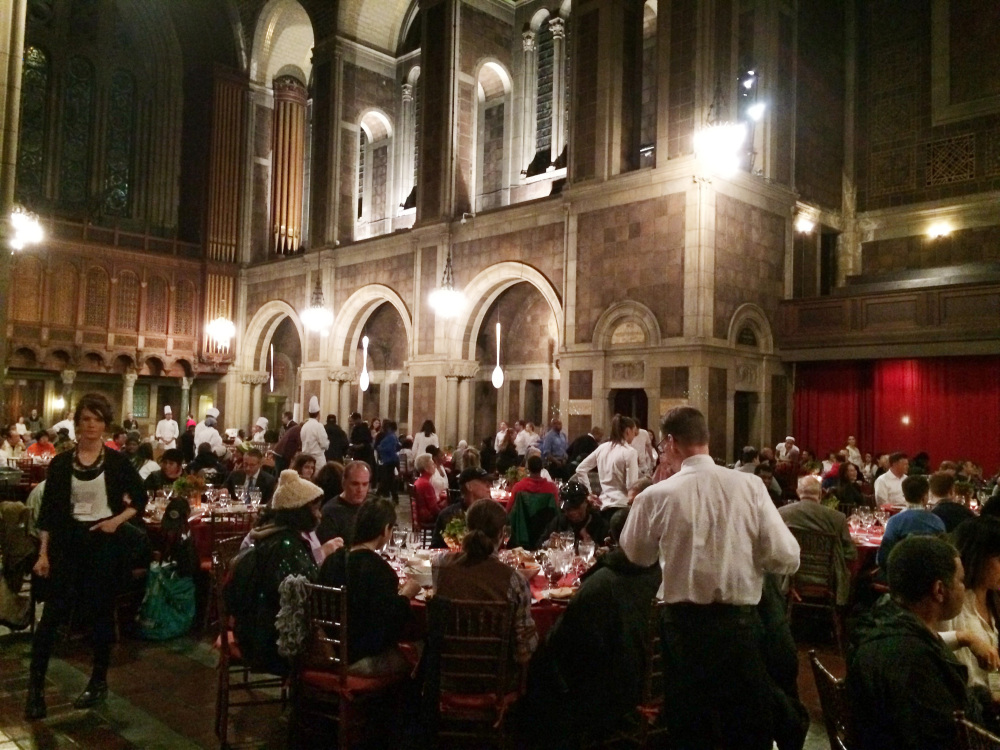 Waiters in white shirts serve dinner to about 500 people at St. Bartholomew's Church in New York on Friday. Some wealthy Manhattan residents paid $100 each for the honor of eating a candlelit holiday dinner with some of the city's homeless.