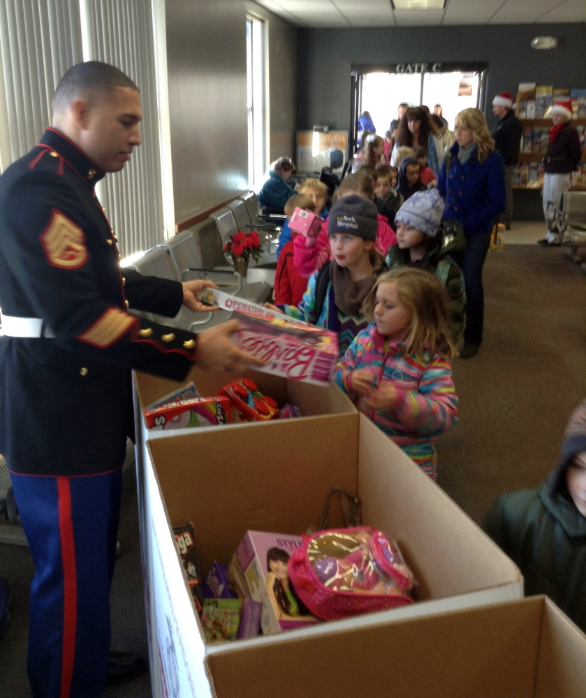 Wells Elementary School students deliver Christmas presents in Portland recently as part of their annual giving campaign to benefit Toys for Tots. The project was administered by U.S. Marine Corps members, who received the donations and spoke to the children about how the program works. The students, their teachers and a few parents traveled to Portland on the Amtrak Downeaster, a journey the school has made annually since 2010. Photo by Reg Bennett.