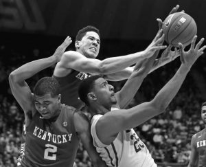 KENTUCKY GUARD Aaron Harrison (2), guard Devin Booker, and LSU forward Jordan Mickey (25) battle for the ball in the second half of an NCAA college basketball game in Baton Rouge, La., on Tuesday. Kentucky won 71-69.