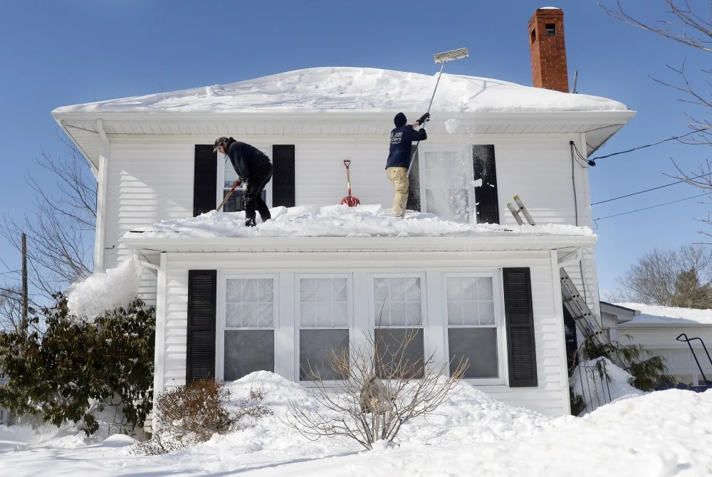 Portland Property Services employees Larry Goodno, left, and Lewis Jarrett clear snow Wednesday off a house on Brighton Avenue in Portland. For homeowners who want to do the work themselves, if they don't already have a roof rake they might not be able to find one in the sold-out stores.