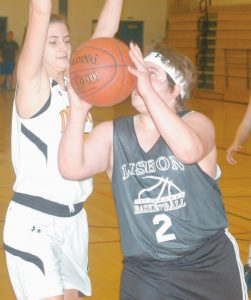 LISBON'S JAKE PATENAUDE, right, puts up a shot against Brunswick's Ketty Stinson. The Greyhounds earned a 34-32 victory on Tuesday to move on to the Unified State Championship in Lewiston. See story, page B1.