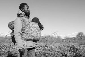 JEAN-PAUL APETEY of Ivory Coast helps carrying a baby near the village of Udovo, Macedonia, in this March 3 photo. The tide of hopeful migrants pours through the vulnerable 'back-door' countries in the hope of entering the 28- nation European Union, and although most people don't make it, the human tide continues to grow, according to Frontex, the EU agency that helps governments police the bloc's leaky frontiers.