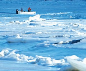 MEN USE A BOAT in an attempt to break ice on Thursday on the Royal River in Yarmouth. A state panel met Thursday to assess snowpack and ice conditions in Maine to determine the potential for spring flooding.