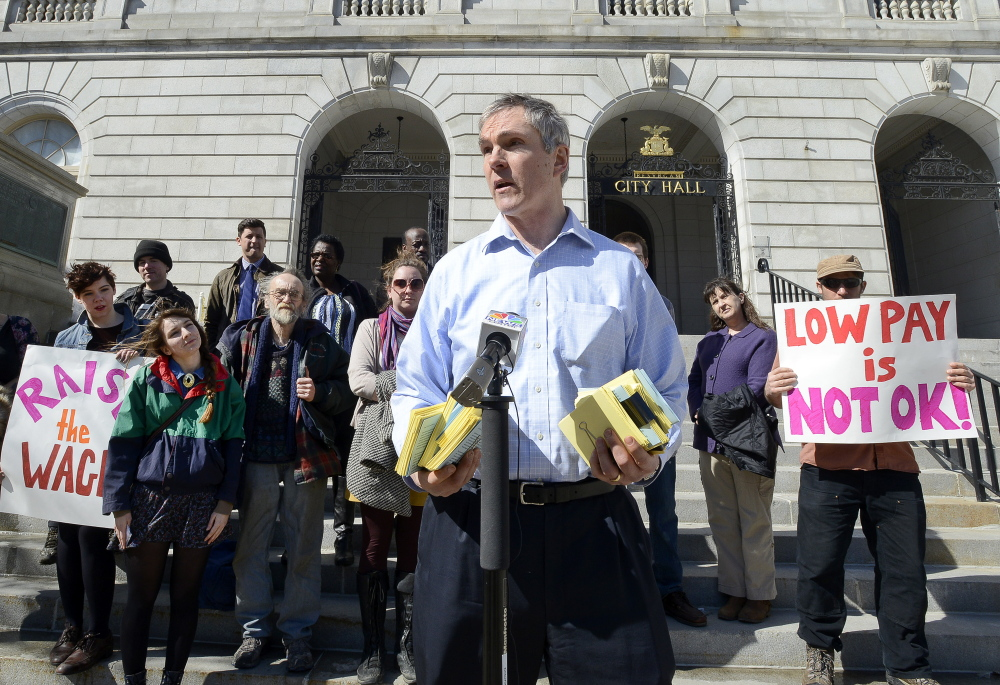 More than a dozen advocates gathered at Portland City Hall last month to deliver postcard petitions to City Councilor Jon Hinck, shown speaking, that asked for action on increasing the minimum wage.