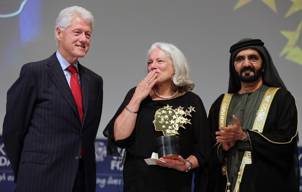 Educator Nancie Atwell responds to applause after receiving the first Global Teacher Prize. With her on stage in Dubai are former President Bill Clinton and Sheikh Mohammed bin Rashid Al Maktoum, the ruler of Dubai.