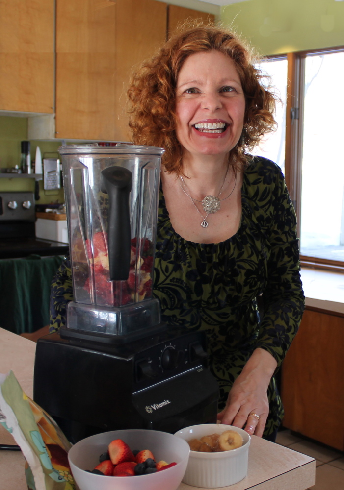 """Lisa Whited poses by the makings of a smoothie in her Portland kitchen. She went vegan in 2013 after attending a lecture called """"Power Foods for the Brain."""""""