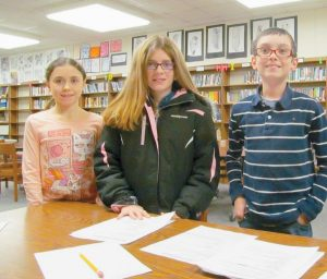 IN CELEBRATION OF APRIL being National Poetry Month, students at Lisbon's Philip W. Sugg Middle School will be participating in the annual poetry contest supported by district librarian Katy Dodge and assistant Tim Gaudet. Junior Volunteers, from left, Amber Soucy, Celeste Brissette and Geoffrey Shambarger, prepare their entries for the contest, which will run from April 13-17. Library windows at the 4 Sugg Drive campus will display the title, author and first line of 30 different poems. Students are required to research and write the poem's second line on their individual entry form for the contest. The poems include old and new classic pieces by Maya Angelou, Longfellow, Shell Silverstein and Ogden Nash, in addition to some famous lyrics from songs about the Civil War and the wild, wild west. Poetry contest winners will be drawn after spring vacation on Monday, April 27. The winners will celebrate with a pizza party on Wednesday, April 29. For more information, contact Gaudet at 353-3055 or email tgaudet@lisbonschoolsme.org.