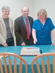 DEPUTY SECRETARY OF STATE for the Bureau of Motor Vehicles Patty Morneault, left, and Secretary of State Matthew Dunlap look on as Topsham BMV service representative Nicole Parent cuts the cake in celebration of the office's new location at 125B Main St., on Monday, March 16.