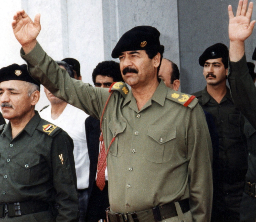 "Iraq's former dictator, Saddam Hussein, center, is shown in Baghdad in 2004. Apologists acknowledge that he perpetrated atrocities but chalk them up to clarivoyance, saying, ""Saddam knew what Iran wanted to do,"" and praising him for understanding the enemy."