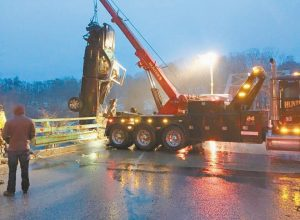 A TRUCK THAT HAD BEEN STOLEN and crashed 80 feet down a riverbank near the Lisbon-Durham bridge Friday morning is hauled up by a tow truck.